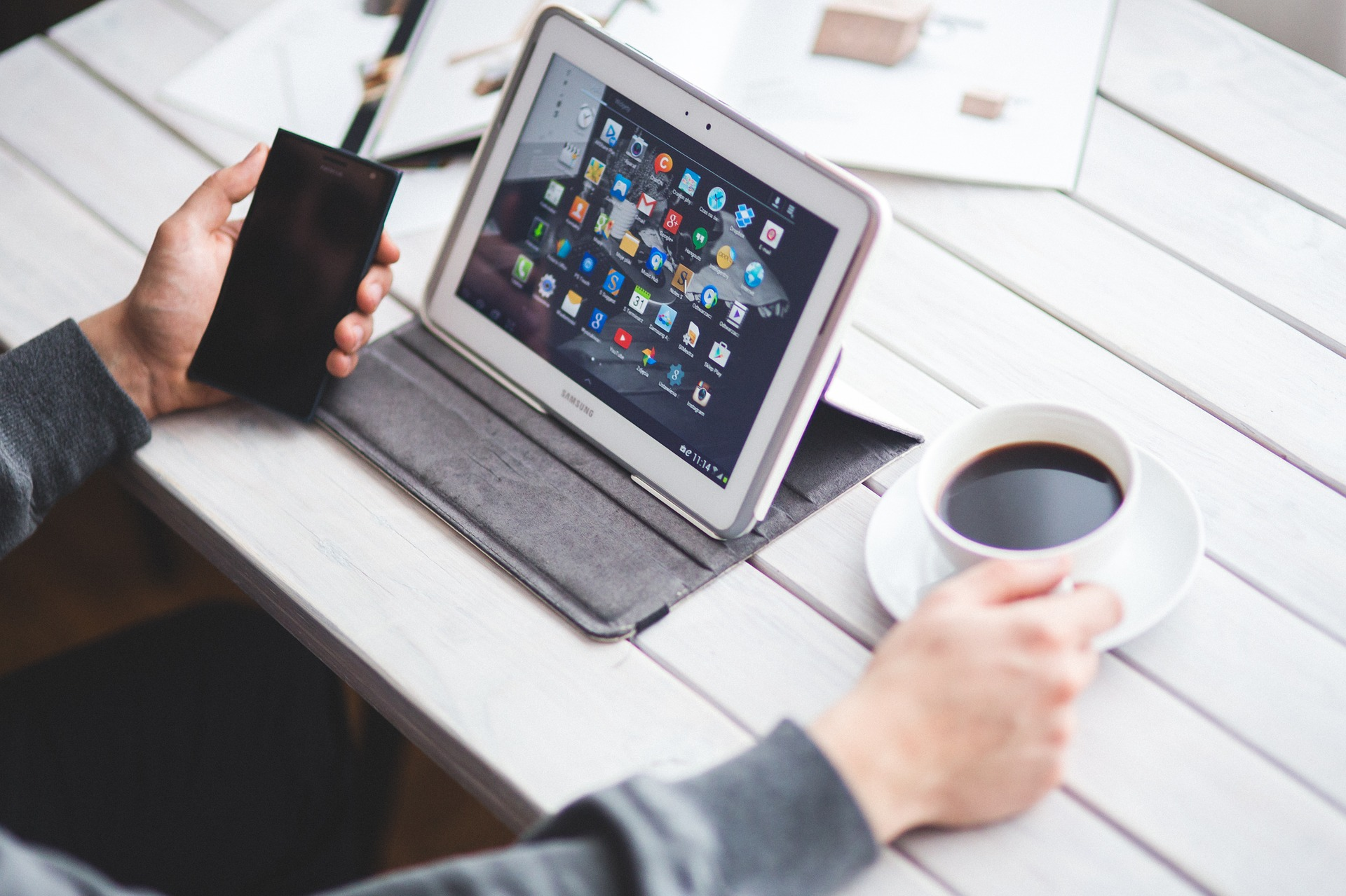 Person Uses a Smartphone and a Laptop at the Same Time While Seated at a Wooden Table with a Cup of Coffee