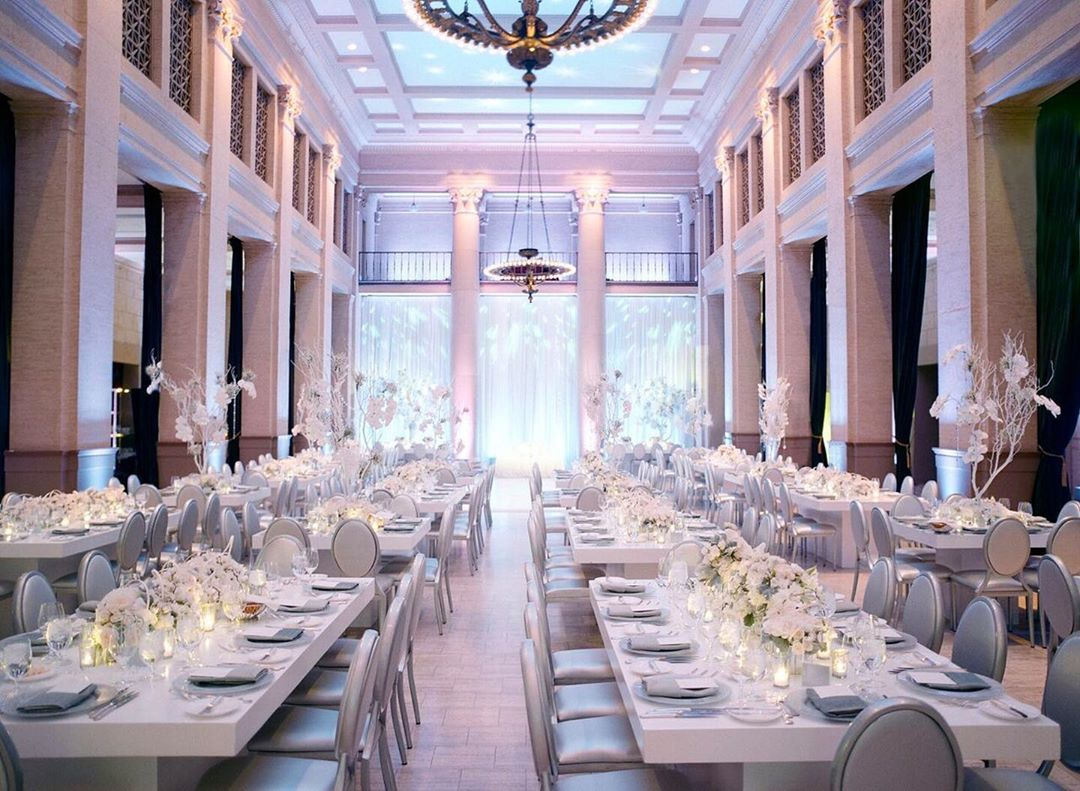 Event space decorated with elegant white columns, tables, and place settings