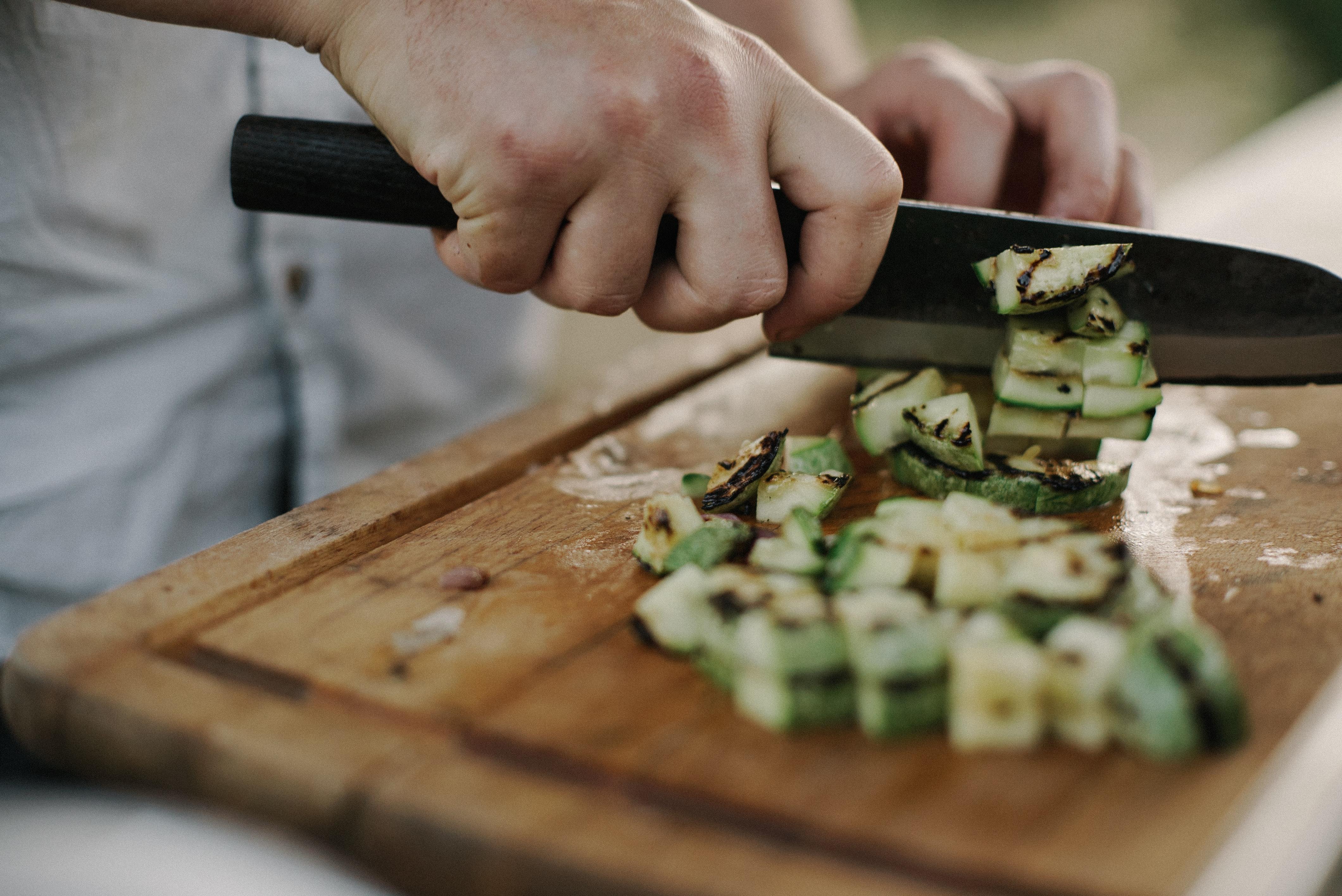 Hands Cutting Zucchini in a Bright Modern Kitchen