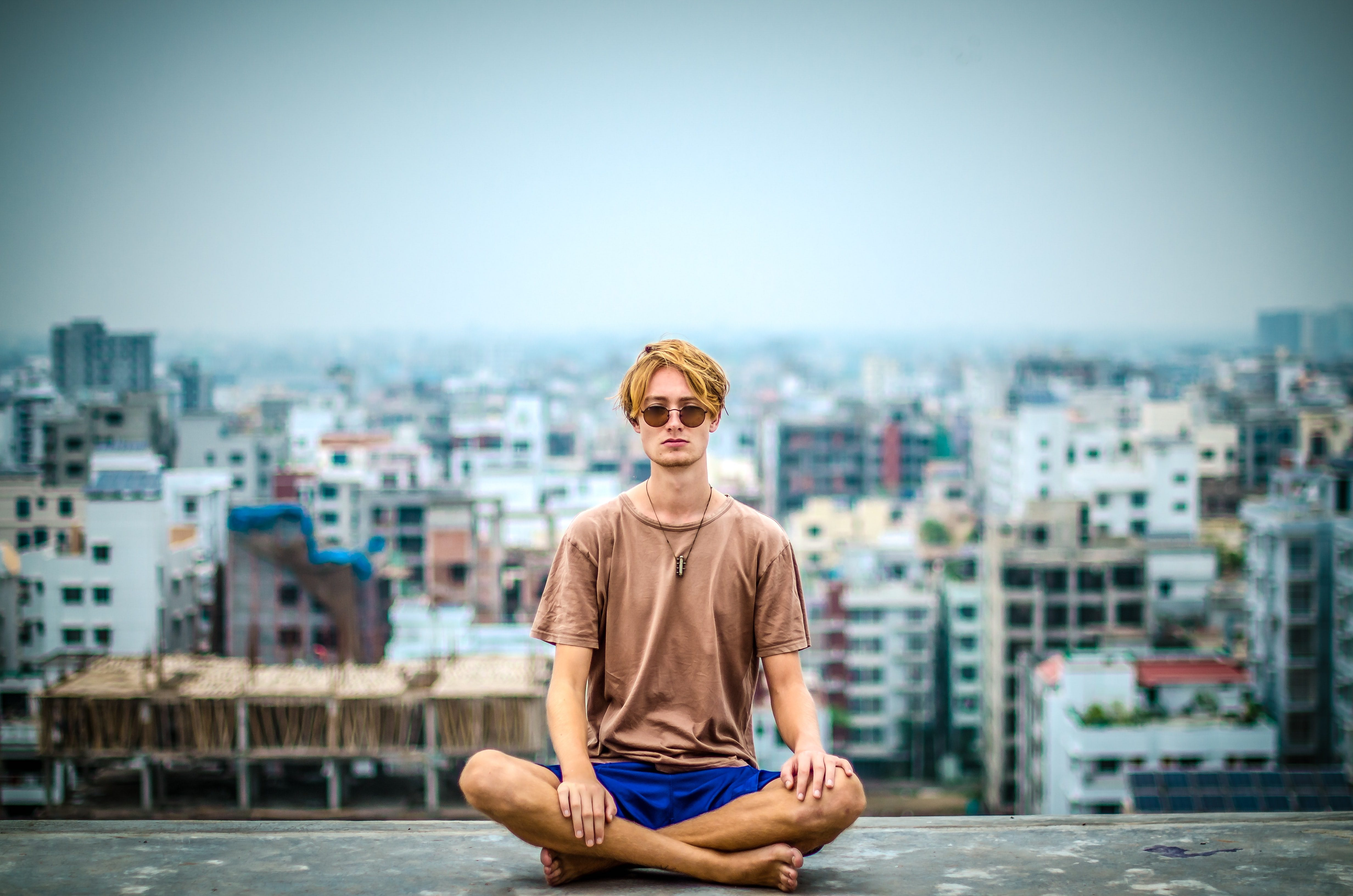 Man meditates on a rooftop against a cityscape backdrop