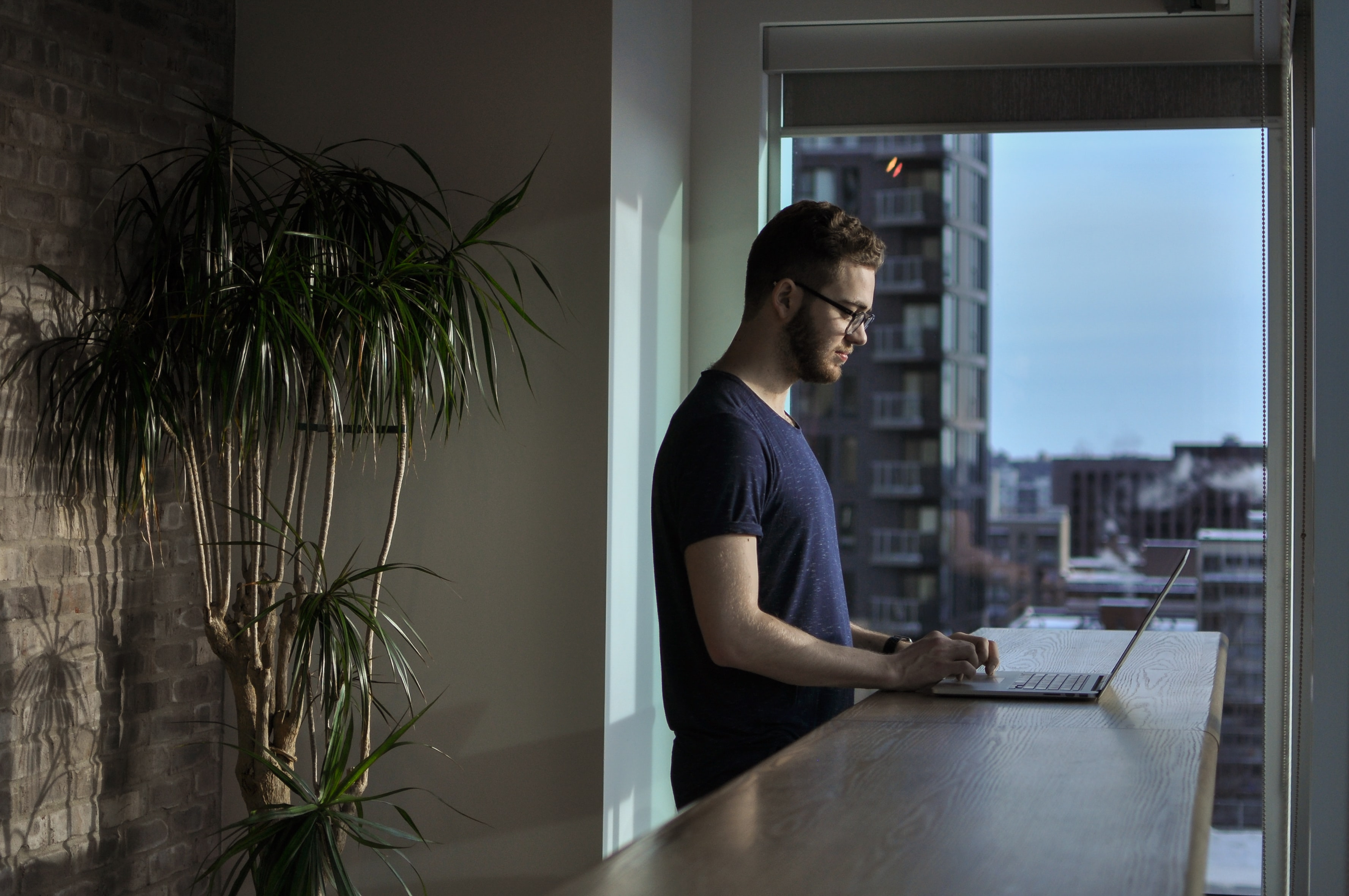 Man Stands at a Wooden Home Countertop While Using a Laptop in Front of a Floor to Ceiling Window