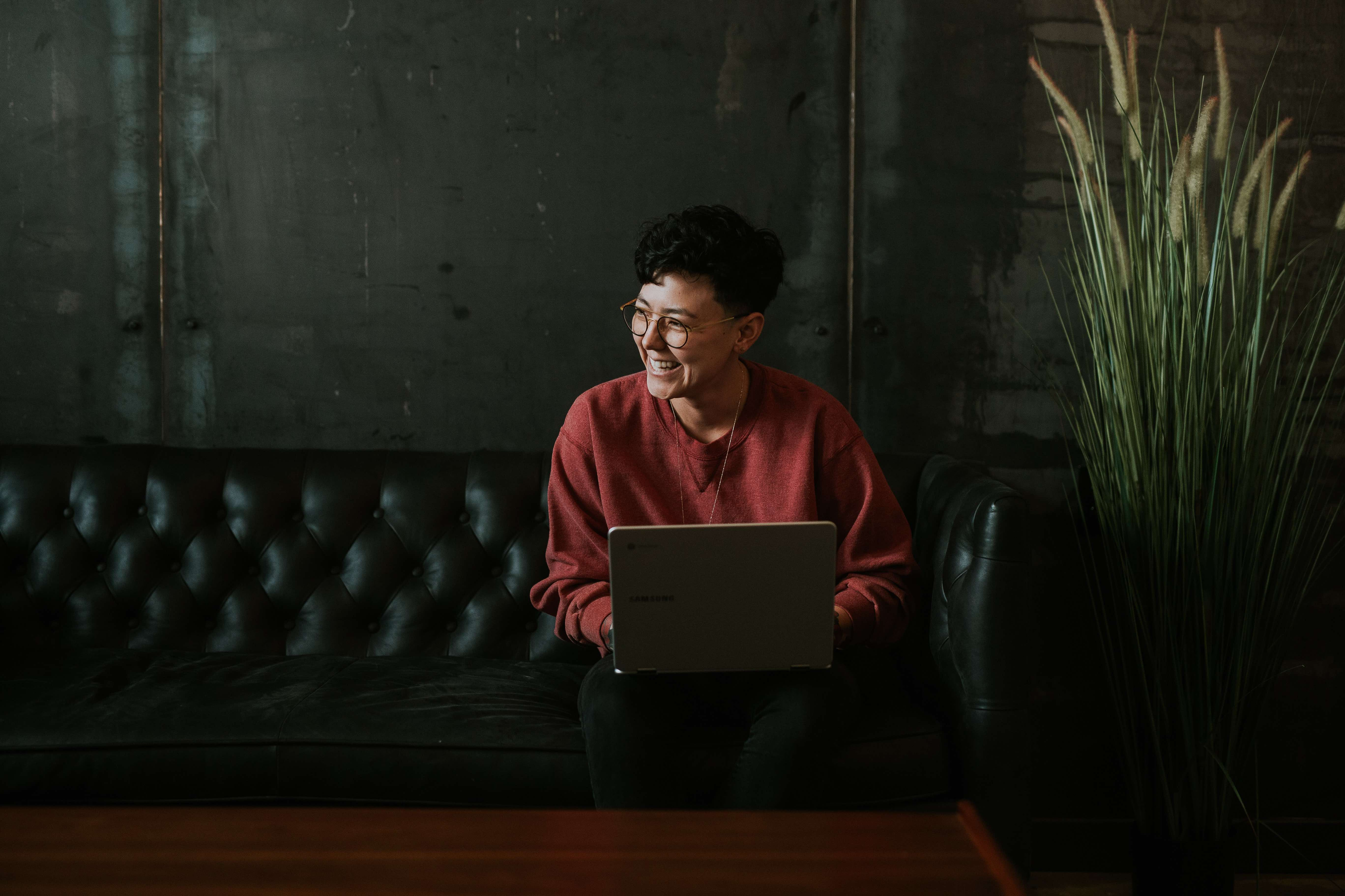 Woman on Black Leather Couch uses a Laptop While Smiling
