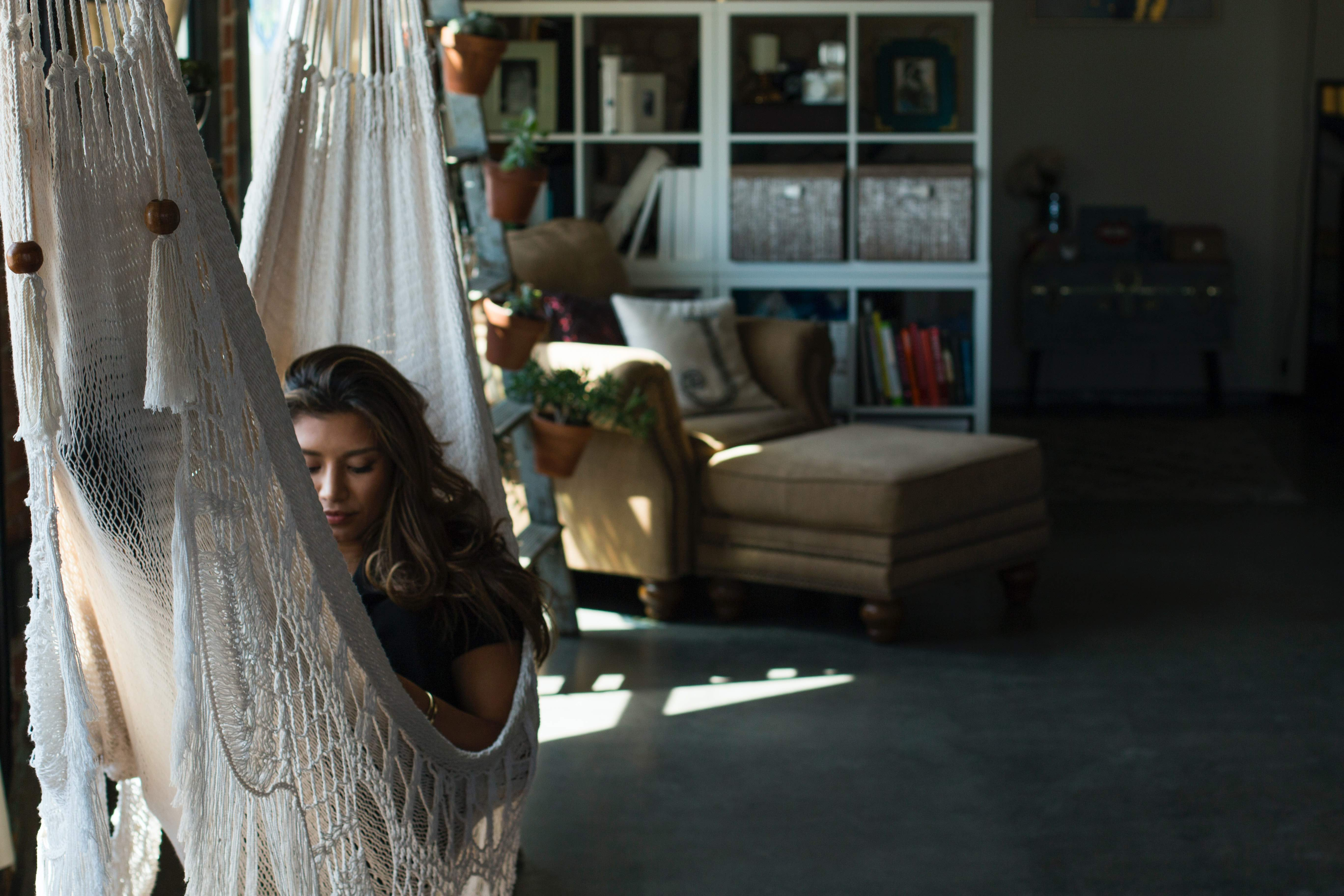Woman rests in a white night hammock at daytime