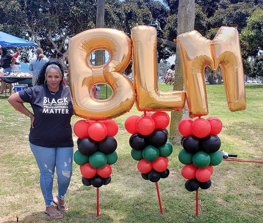 Black Lives Matter balloon arrangement displayed in a field