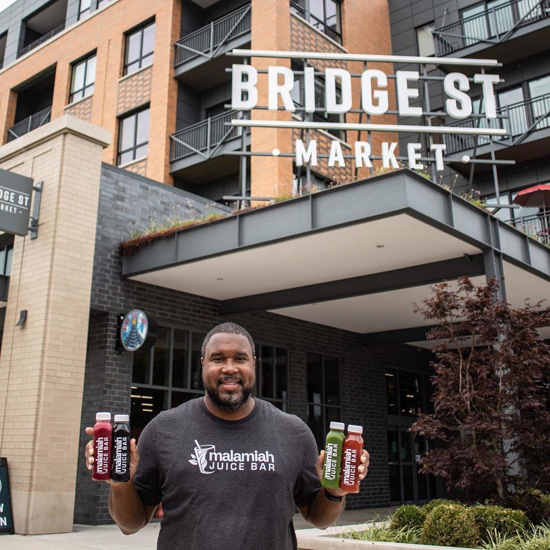 Black man poses holding bottles of Malamiah Juice Bar juice