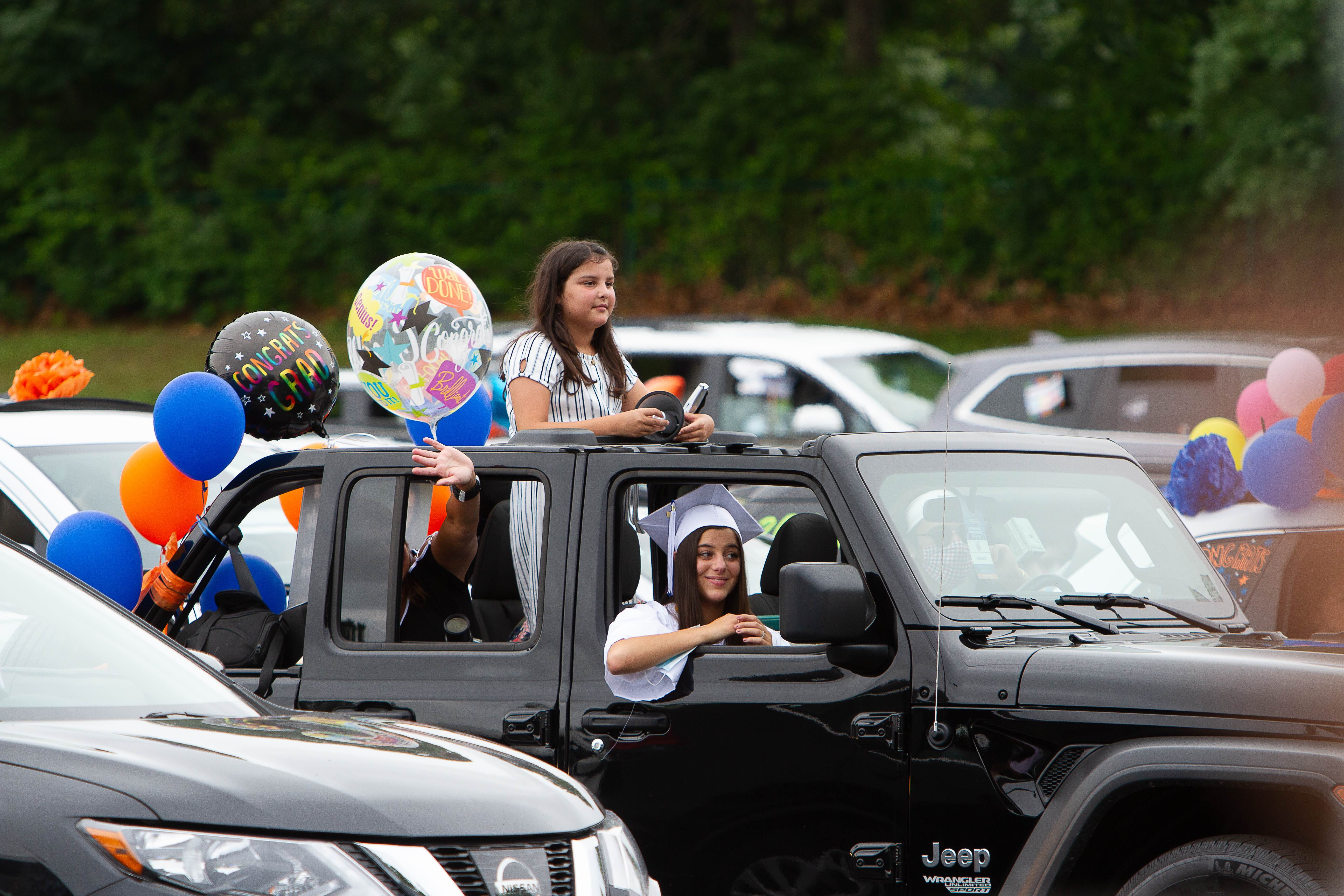 Car with a smiling graduate and her family parked in the Toyota Presents Oakdale Theatre lot