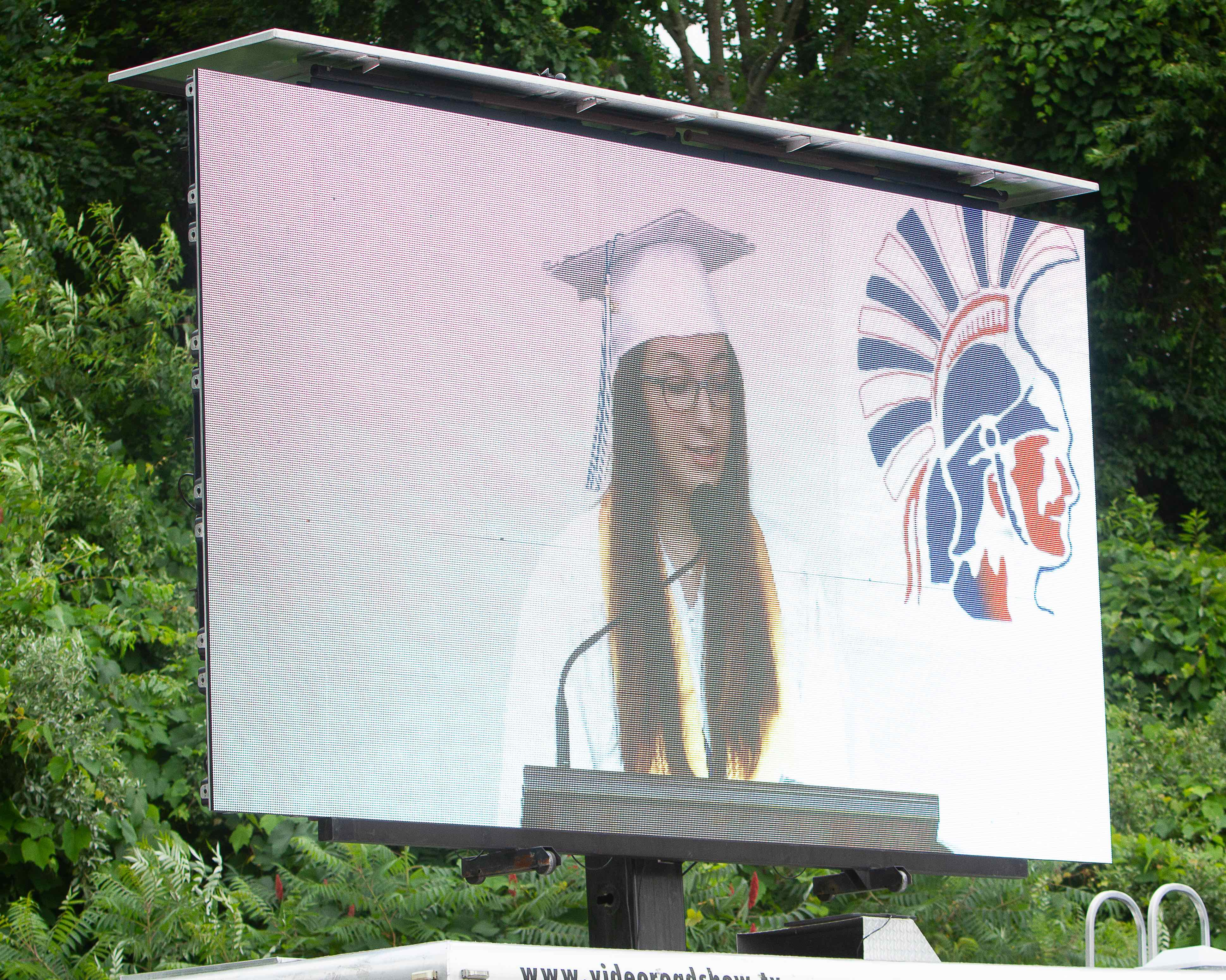 LED screen displays a graduate making a speech in the Toyota Presents Oakdale Theatre lot