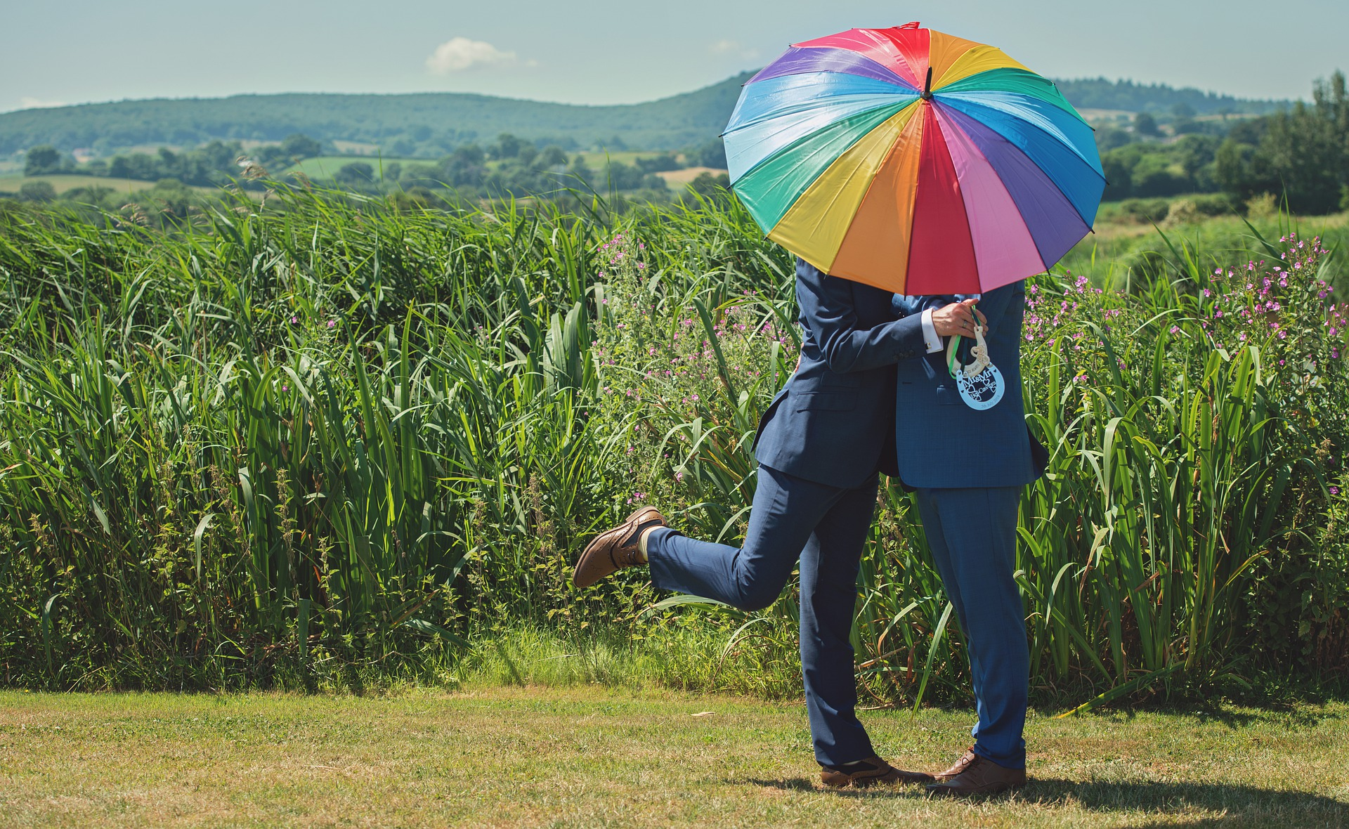 grooms kissing under rainbow umbrella