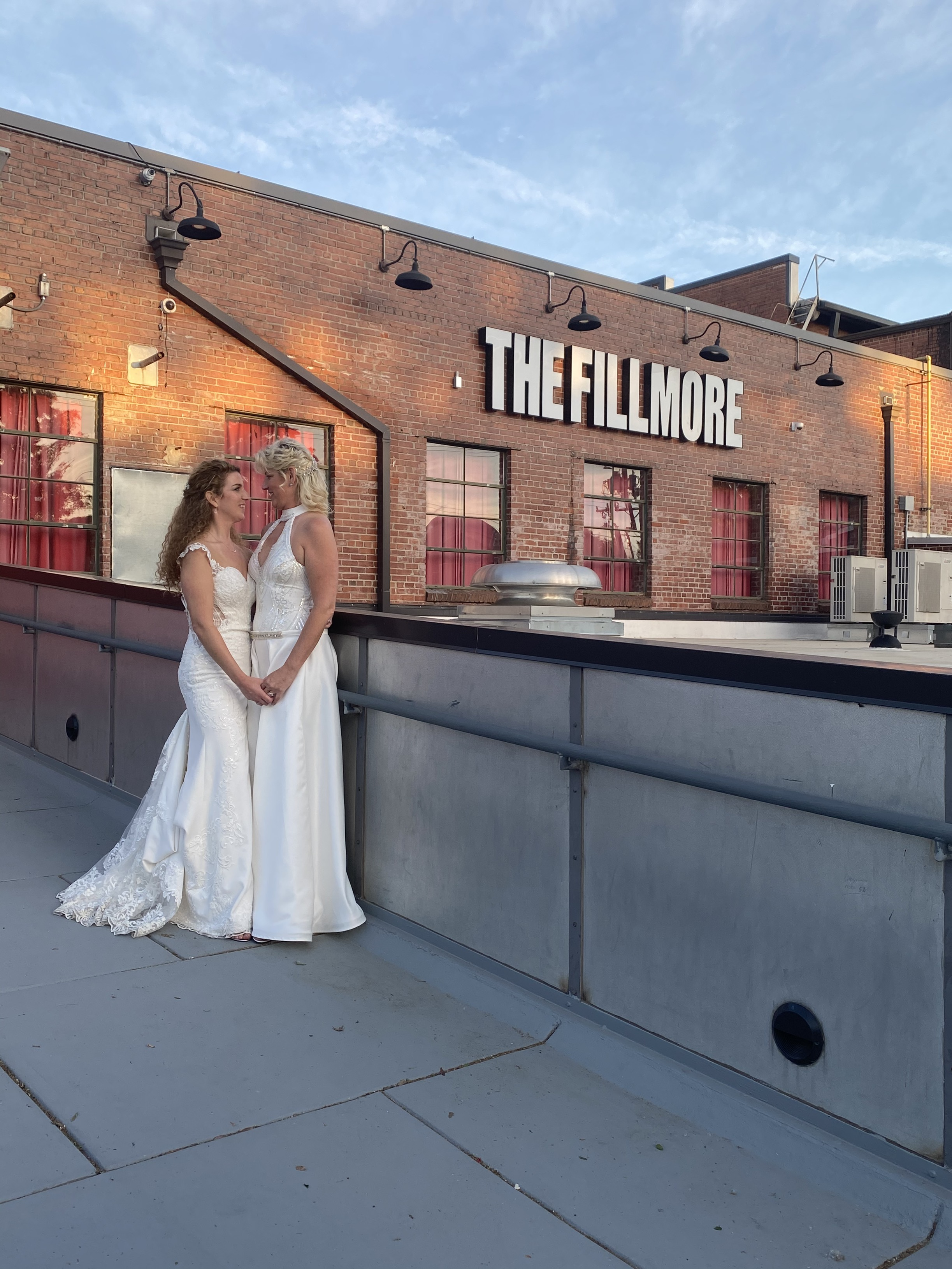 two brides pose outside of fillmore charlotte