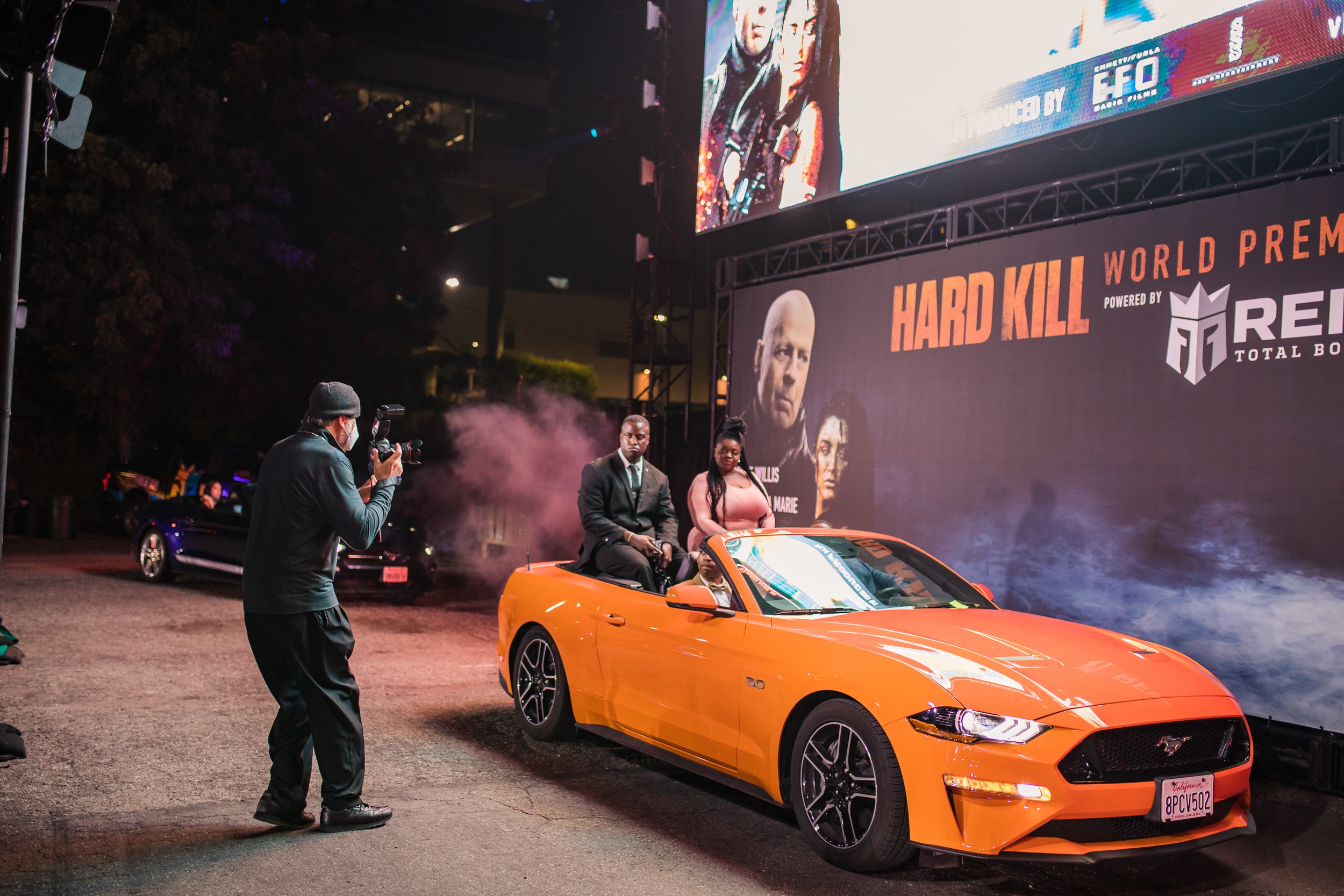 Guests drive through the drive and repeat carpet orange sports car Hard Kill billboard